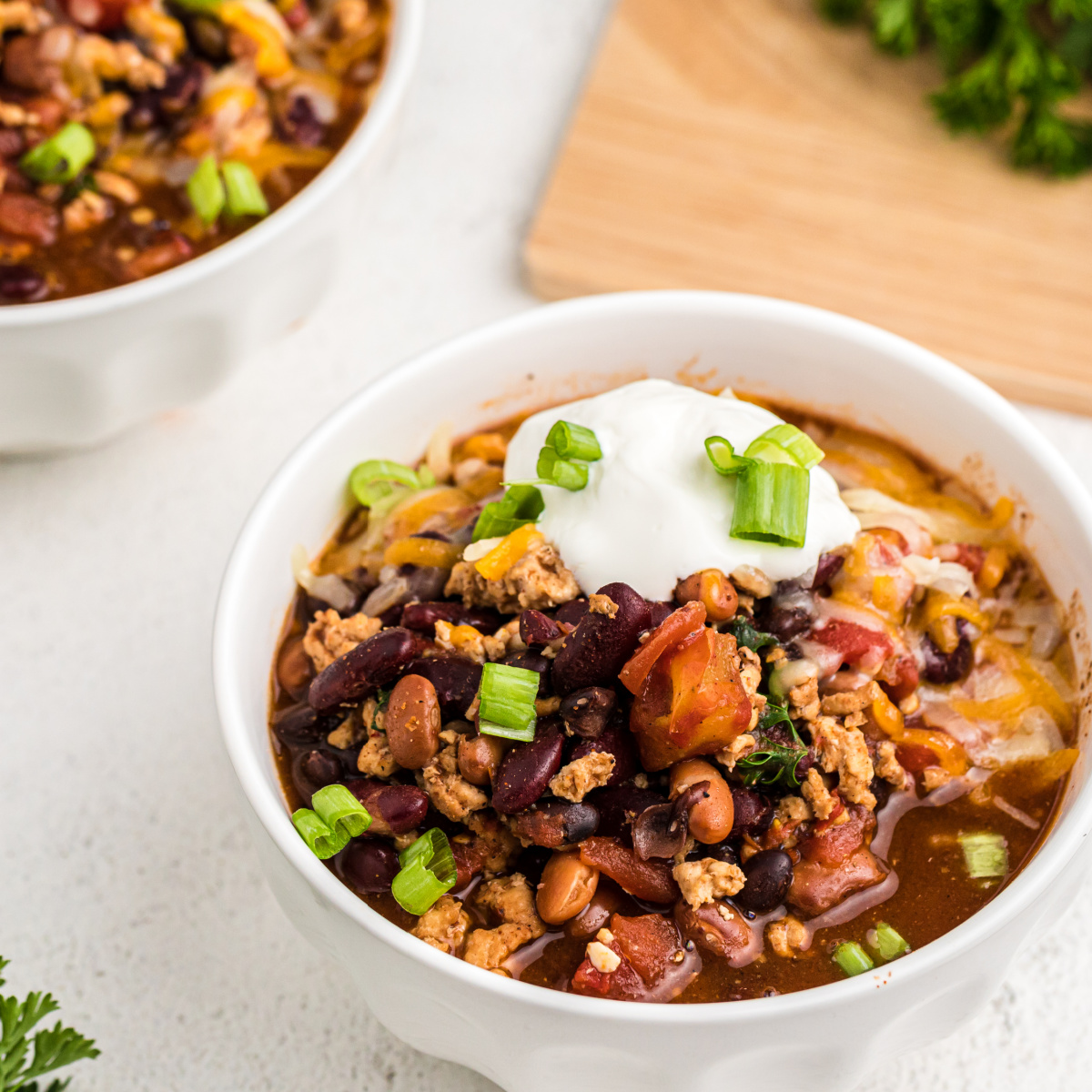 Slow Cooker Turkey Chili with toppings in a white bowl.