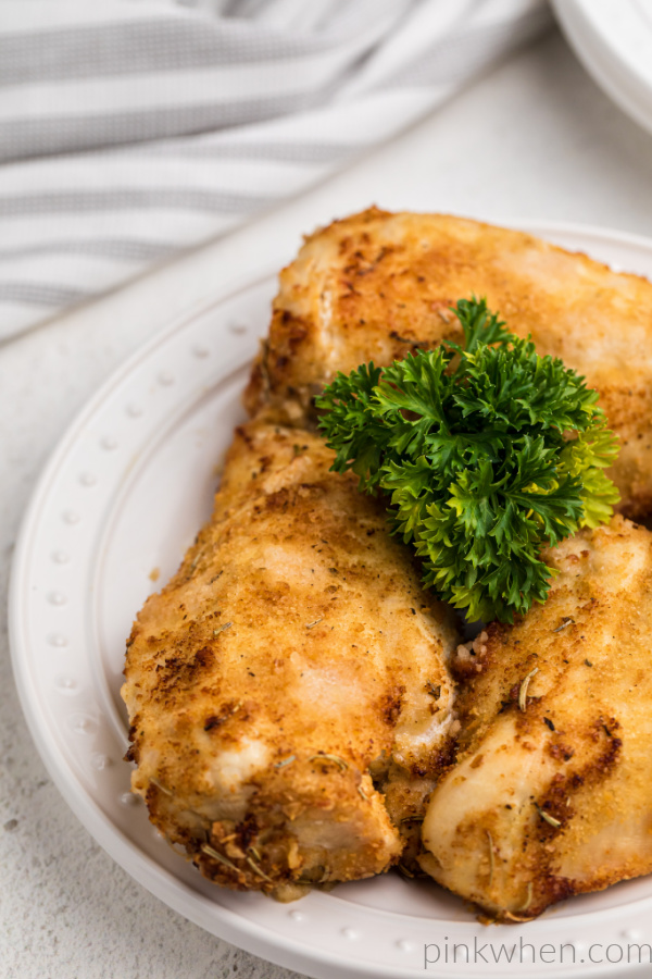 Chicken breasts made in the air fryer on a white plate and ready to serve.