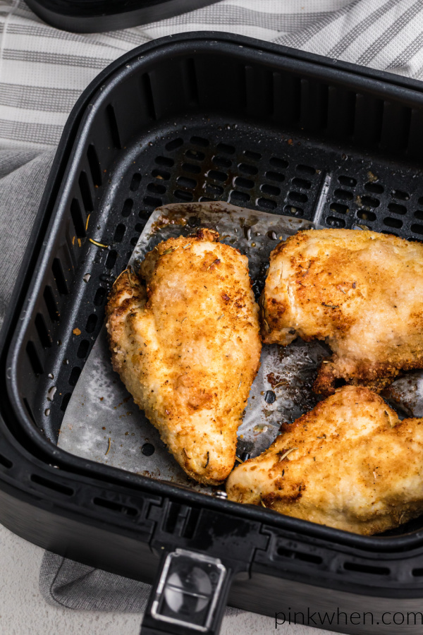 Cooked chicken breasts in an air fryer.