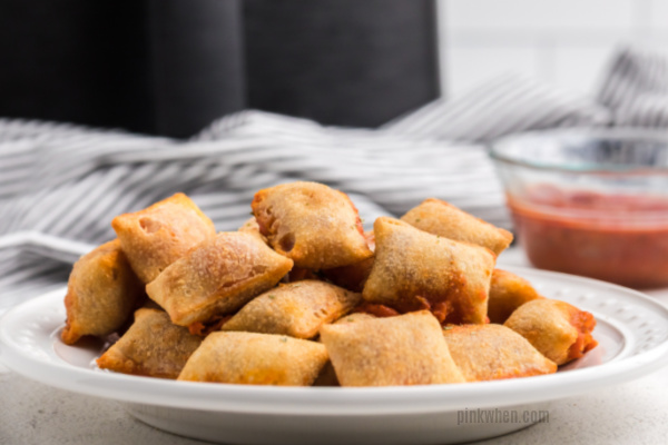 Freshly baked pizza rolls from air fryer on a white plate ready to serve.