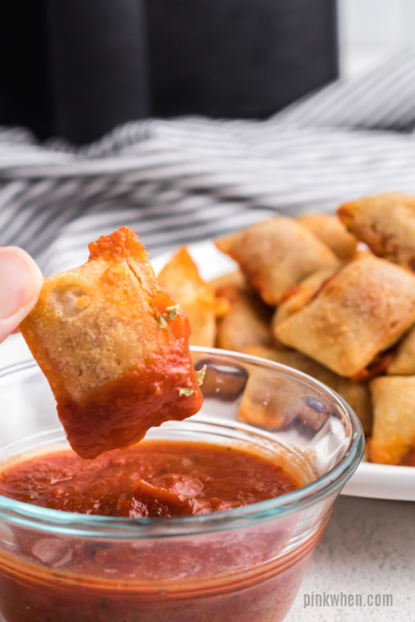 air fryer pizza roll being dipped in pizza sauce.