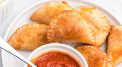 Homemade Air Fryer Pizza Rolls on a white plate with pizza dipping sauce.