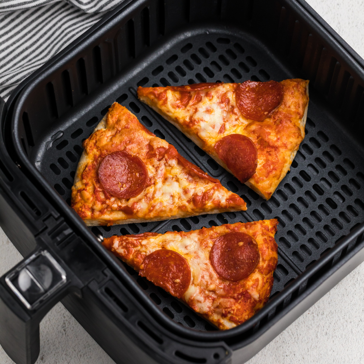 Pizza slices in an air fryer basket.