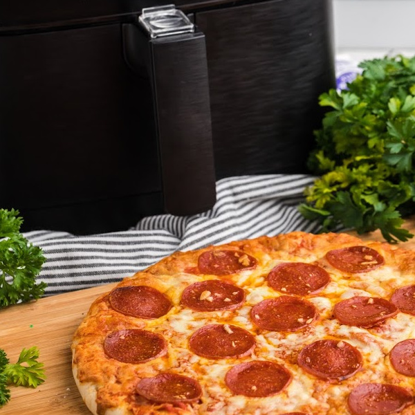 Pizza on a cutting board with a air fryer in the background.