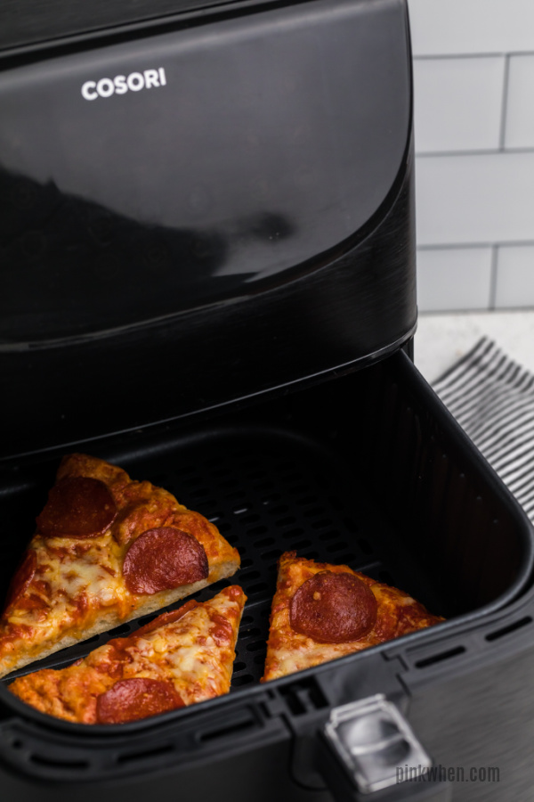 Pizza slices in an air fryer basket ready to be removed.