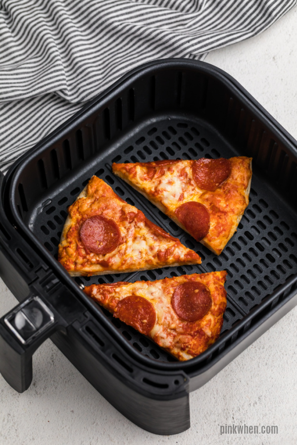 Slices of pizza in an air fryer basket.