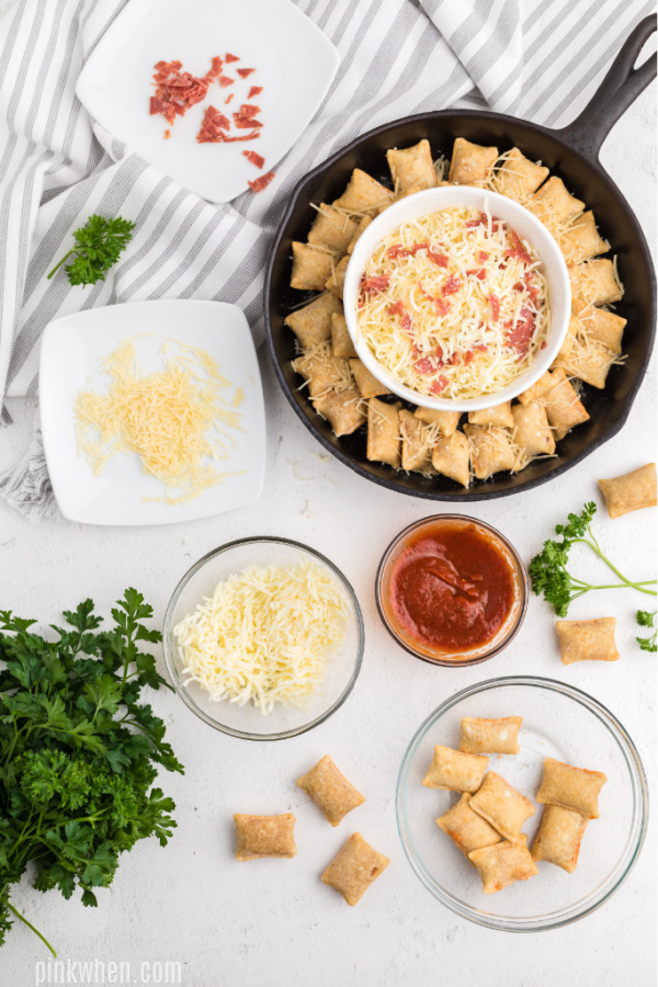 Pizza dip and pizza rolls covered in parmesan cheese and ready to bake.