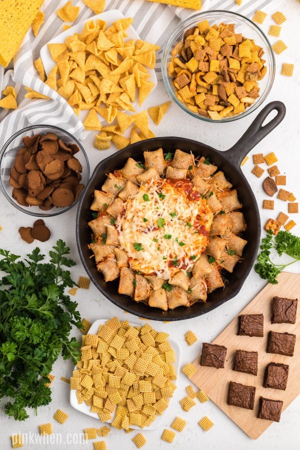 Skillet pizza rolls and pizza dip on a table full of snacks.