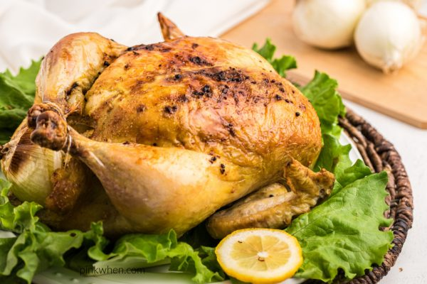 Roasted chicken on a bed of luttuce ready to carve and serve.