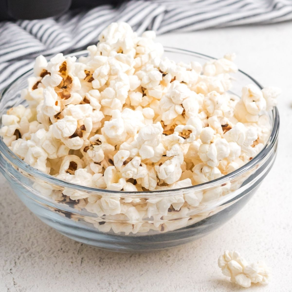 Popcorn in a clear bowl from an air fryer.