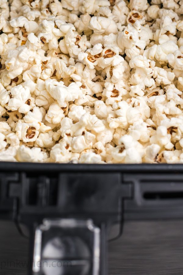 popcorn in an air fryer basket ready to serve.