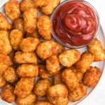 Tater Tots from an Air Fryer on a white plate with a bowl of ketchup.
