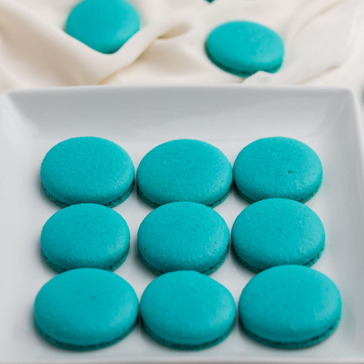 Blue Macaron cookies on a white plate.