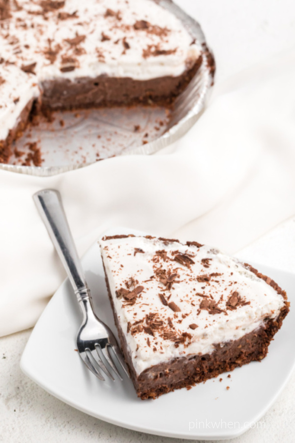 Slice of chocolate cream pie on a white plate ready to eat.