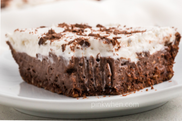 Slice of chocolate cream pie with a bite missing.