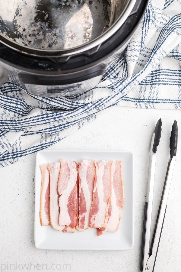 Halved slices of bacon on a white plate.