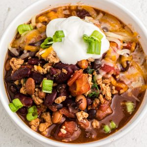 Pressure Cooker Turkey Chili in a white bowl and topped with sour cream and green onion tops.