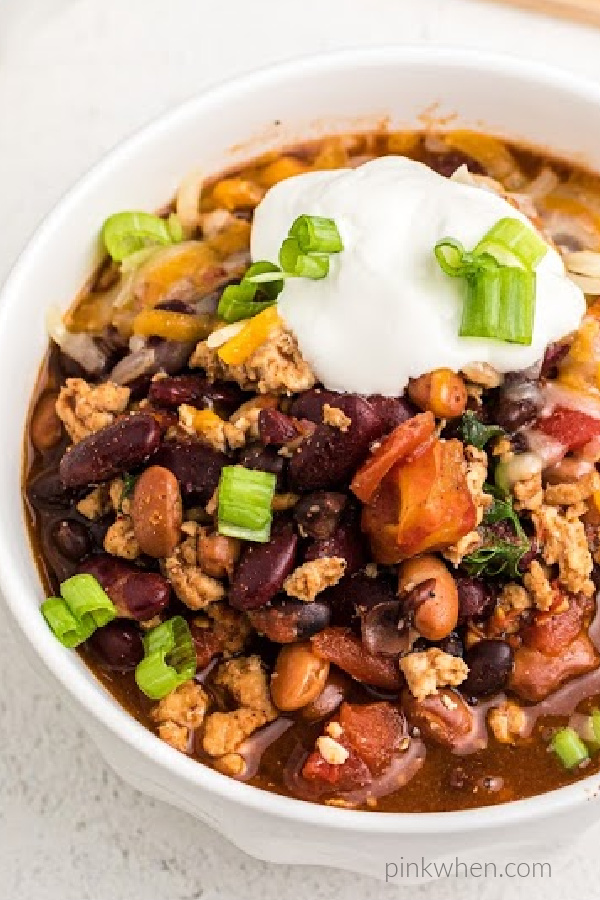 Turkey Chili in a bowl topped with sour cream and green onion tops.
