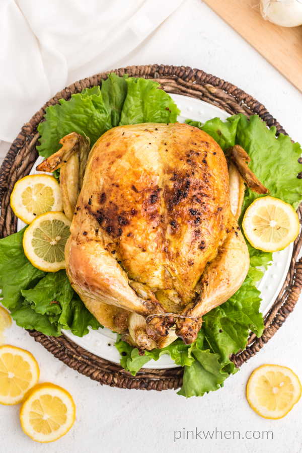 Slow roasted Chicken on a plate with lettuce and lemons.