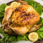 Slow Roasted Whole Chicken on a bed of lettuce with lemons.