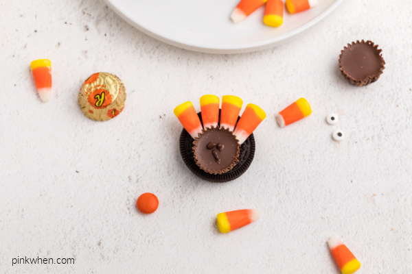 Candy corn and reese's cup on top of an OREO cookie.