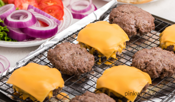 Oven baked hamburgers with cheese and plain that are fully cooked and ready to eat.