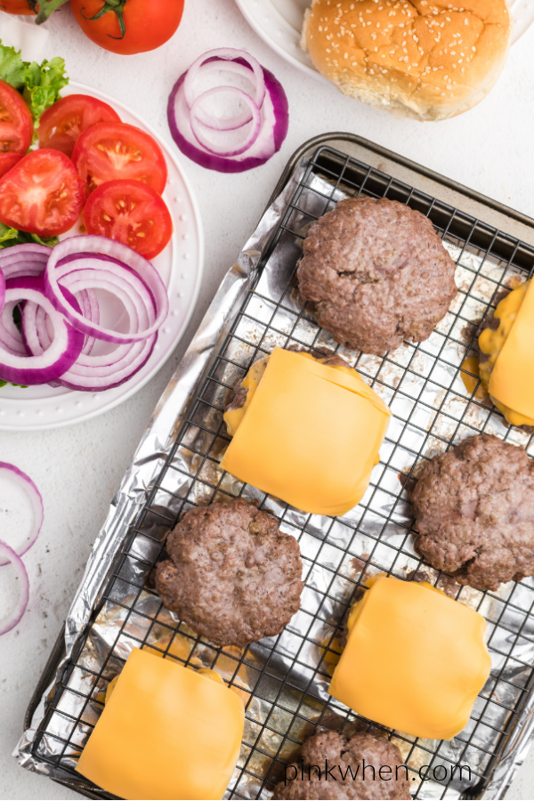 Oven baked hamburgers with cheese and plain burgers on a cooling rack over a cookie sheet.