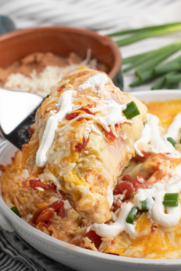 Taco casserole made with chicken being scooped from a white casserole dish.
