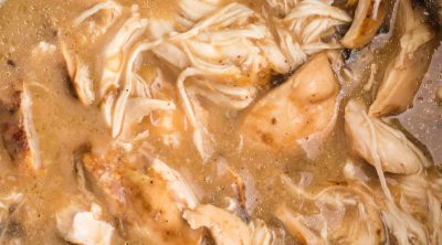 Shredded Chicken with gravy in the liner of a slow cooker.