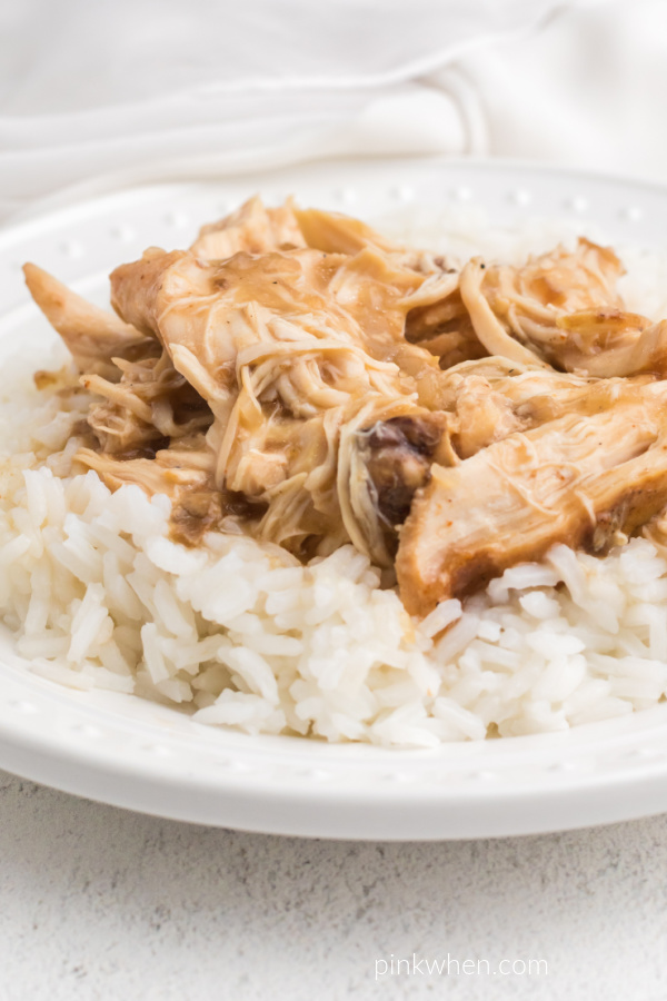 Crockpot Chicken and Gravy served over white rice on a white plate.