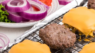 Baked hamburger patty's on a baking sheet with hamburger toppings in the background.