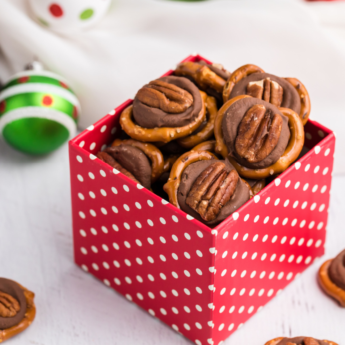 Pretzel Turtles made with Rolo candy in a red box.