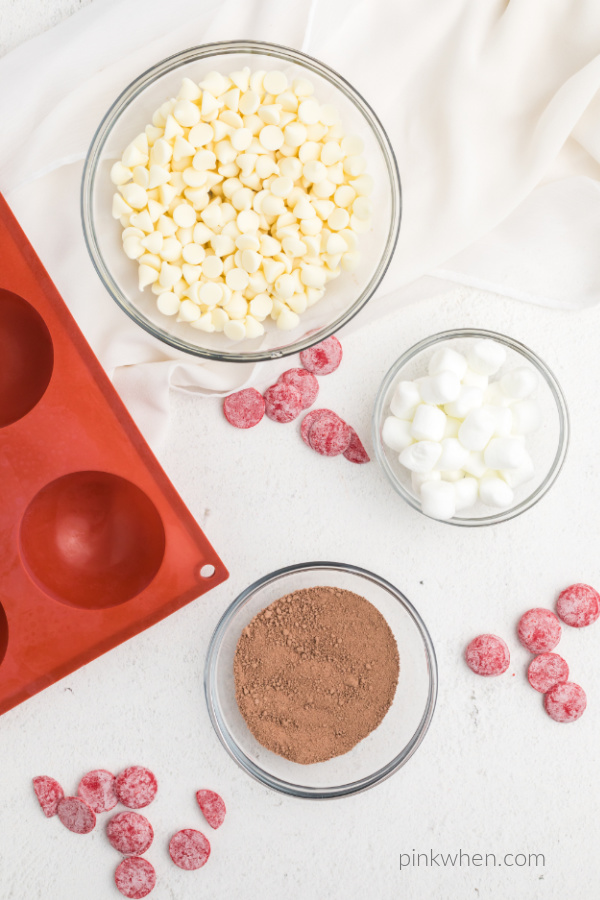 Ingredients on top of a white tabletop used to make hot chocolate bombs for Valentines day.