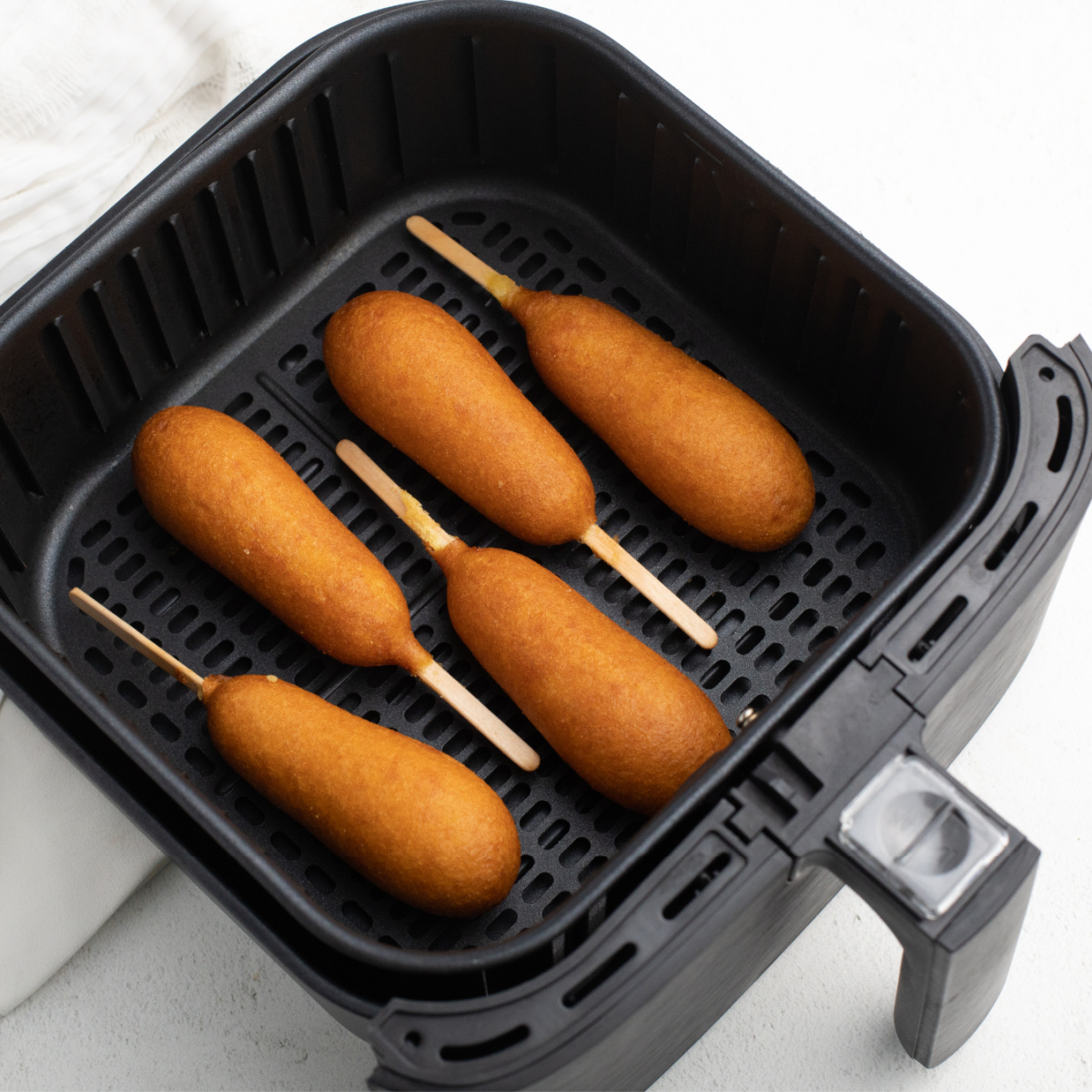 Corn dogs in a single layer in an Air Fryer basket.