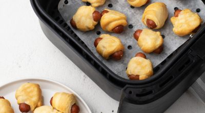 Crescent dogs in an Air Fryer basket and on a white plate.