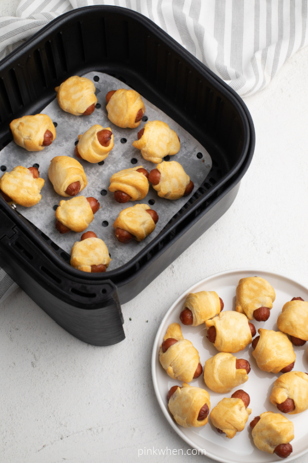 Pigs in a Blanket in the basket of an Air Fryer and on a white plate.