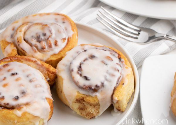 Cinnamon Rolls with glaze and served on a white plate.