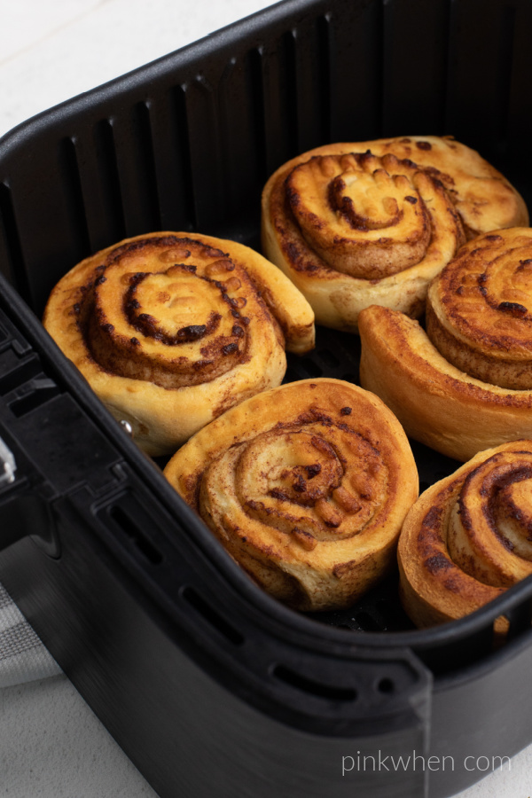 Cinnamon rolls cooked and still in the basket of the Air Fryer.