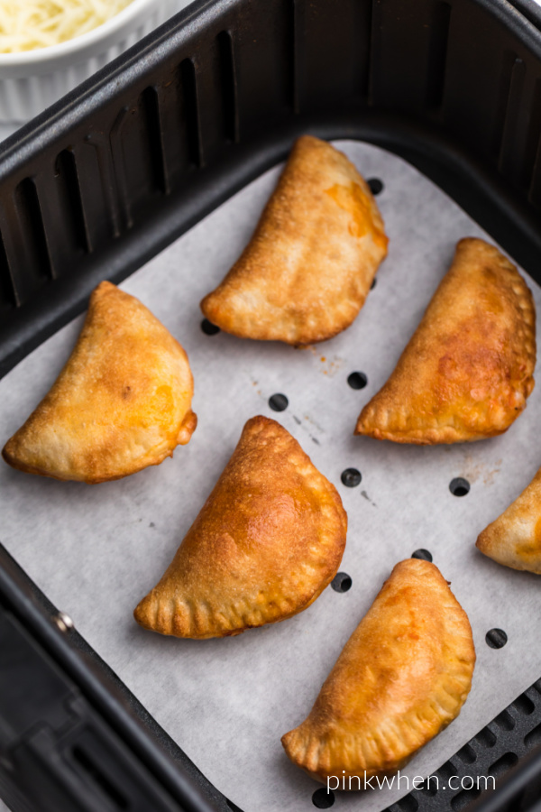 Pizza rolls in the basket of the Air Fryer on parchment paper.