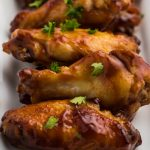Air Fried BBQ Chicken Wings on a white serving dish sprinkled with fresh parsley.