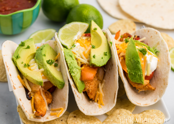 Air Fryer chicken fajitas topped with sour cream, cheese, and avocado slices ready to eat.