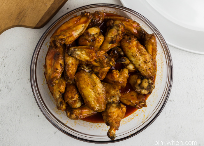 Cooked wings getting tossed in barbecue sauce before serving.