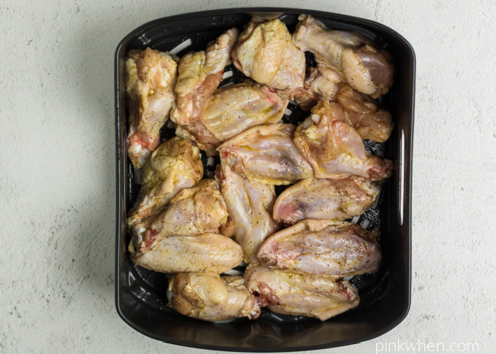 Wings seasoned and ready to cook in the Air Fryer basket.