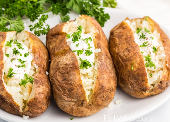 Air Fried baked potatoes on a white plate with sour cream and fresh parsley toppings.