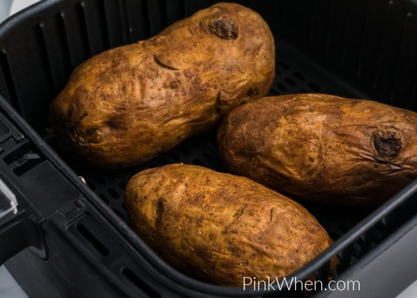 Baked potatoes fully cooked in an air fryer basket.