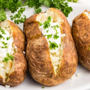 Baked Potatoes topped with sour cream and fresh parsley.