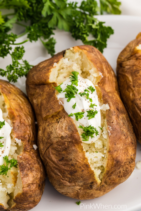 Air Fryer Baked Potatoes are topping with sour cream and fresh parsley and ready to eat!