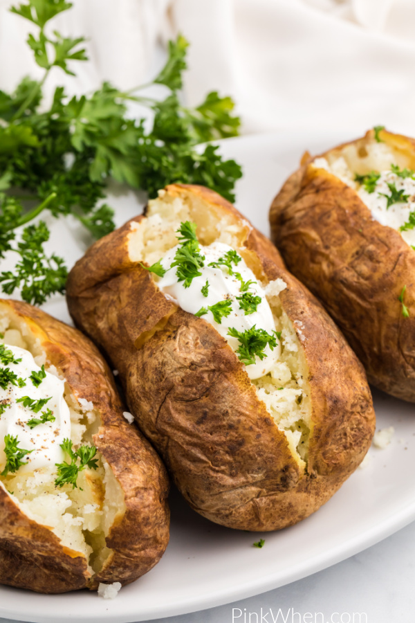 Baked potatoes made in the Air Fryer and topped with sour cream and fresh parsley.