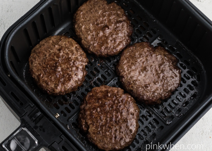 Fully cooked Air Fryer burgers in the basket of the Air Fryer.