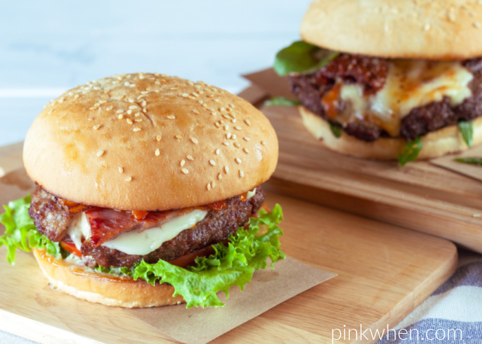 Fully dressed hamburgers with all the fixings on cutting boards and ready to serve.